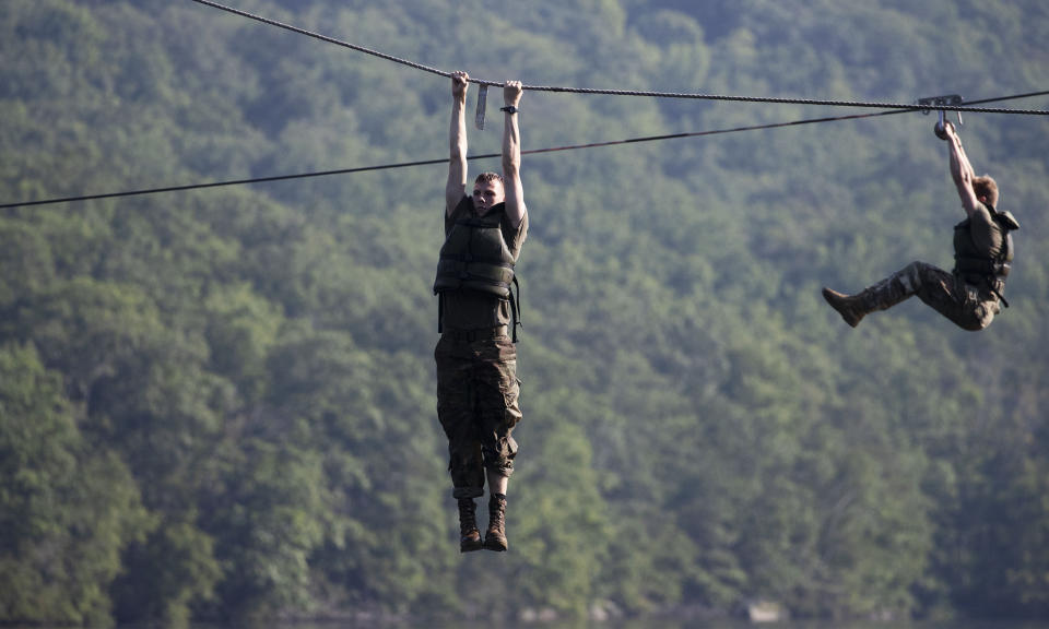 Cadets hang above a lake as they navigate a water obstacle course, Friday, Aug. 7, 2020, in West Point, N.Y. The pandemic is not stopping summer training at West Point. Cadets had to wear masks this year for much of the training in a wooded area just beyond the main gates of the U.S. Military Academy. (AP Photo/Mark Lennihan)
