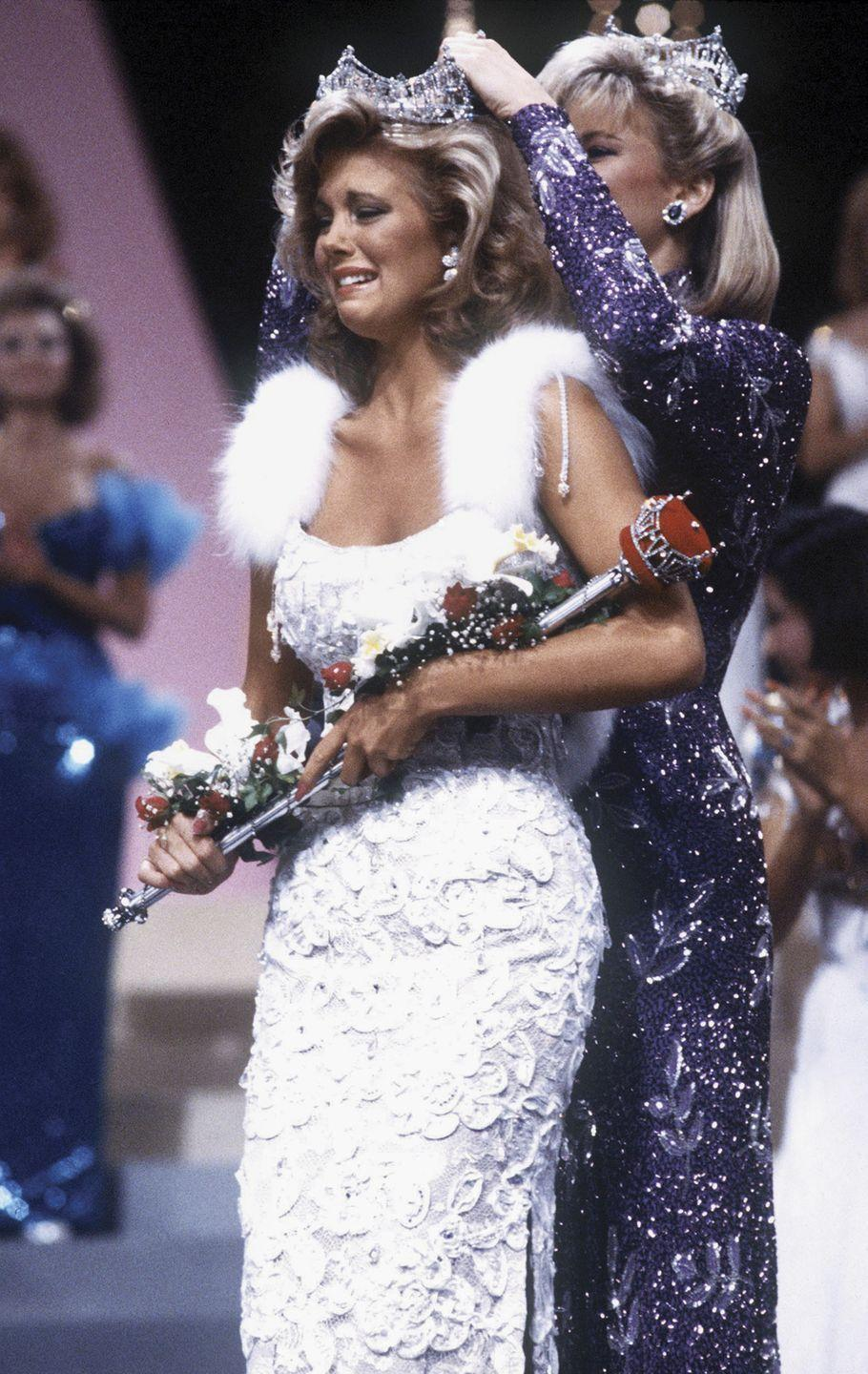 <p>As the '80s went on, the glamour only intensified. Susan Akin from Mississippi did not hold back in this white, embroidered look with fur straps.</p>