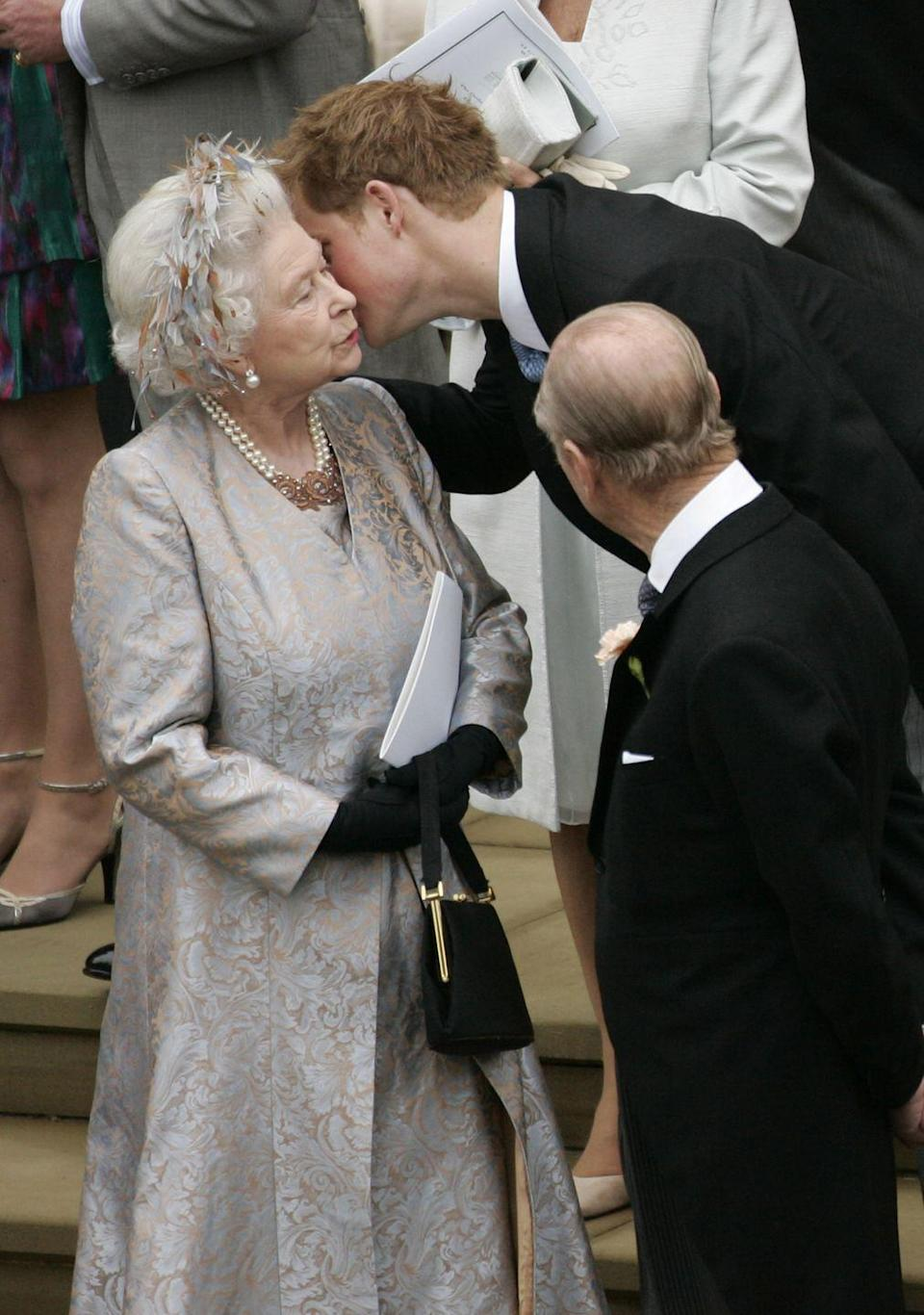 <p>Prince Harry gives his granny a quick peck at the wedding of Peter Phillips to Autumn Kelly. For the occasion, the Queen stepped out in a statement-making hair accessory.</p>