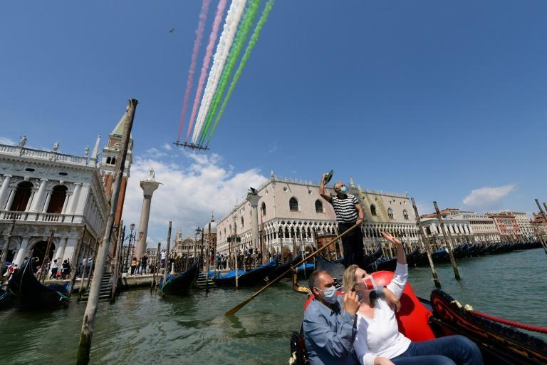 People taking a gondola ride and a gondolier wave as the Italian Air Force aerobatic unit perform over Venice