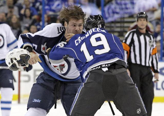 Winnipeg Jets defenseman Mark Stuart (5) loses his helmet as he fights with Tampa Bay Lightning right wing B.J. Crombeen (19) during the first period of an NHL hockey game on Saturday, Dec. 7, 2013, in Tampa, Fla. Both players were given five-minute major fighting penalties. (AP Photo/Chris O'Meara)