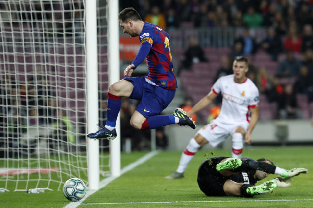 Barcelona's Lionel Messi leaps over Mallorca's goalkeeper Manolo Reina, on the ground, during a Spanish La Liga soccer match between Barcelona and Mallorca at Camp Nou stadium in Barcelona, Spain, Saturday, Dec. 7, 2019. (AP Photo/Joan Monfort)