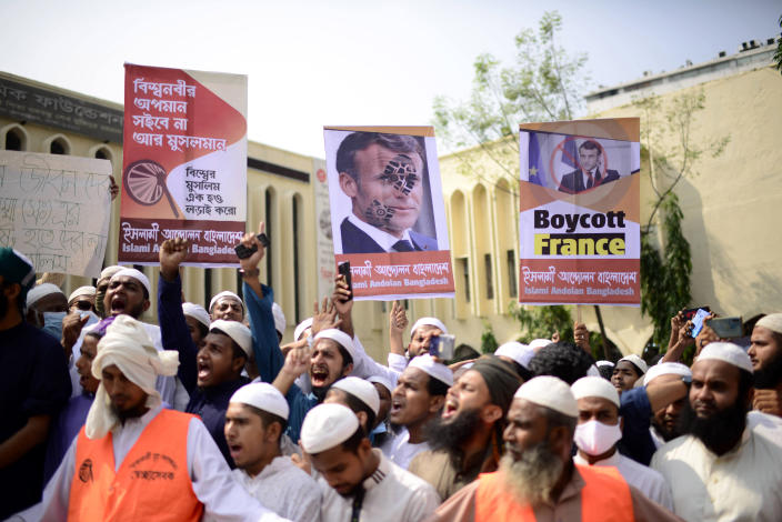 """Supporters of Islami Andolan Bangladesh, an Islamist political party, hold posters of French President Emmanuel Macron as they protest against the publishing of caricatures of the Prophet Muhammad they deem blasphemous, in Dhaka, Bangladesh, Tuesday, Oct. 27, 2020. Muslims in the Middle East and beyond on Monday called for boycotts of French products and for protests over the caricatures, but Macron has vowed his country will not back down from its secular ideals and defense of free speech. Poster reads """"Muslims will not tolerate insults to the prophet. Muslims of the world unite and fight."""" (AP Photo/Mahmud Hossain Opu)"""
