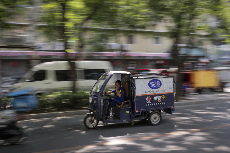 A private delivery company's courier wearing a protective face mask to help curb the spread of the new coronavirus rides his delivery cart passes by a residential area in Beijing, Sunday, June 21, 2020. According to state media reports, nearly one hundred thousand delivery workers have to accept the nucleic acid testing, a countermeasure to prevent the spread of the virus in the capital city. (AP Photo/Andy Wong)