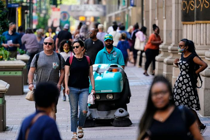 People, some without masks, walk along Market Street in Philadelphia, Friday, May 21, 2021.