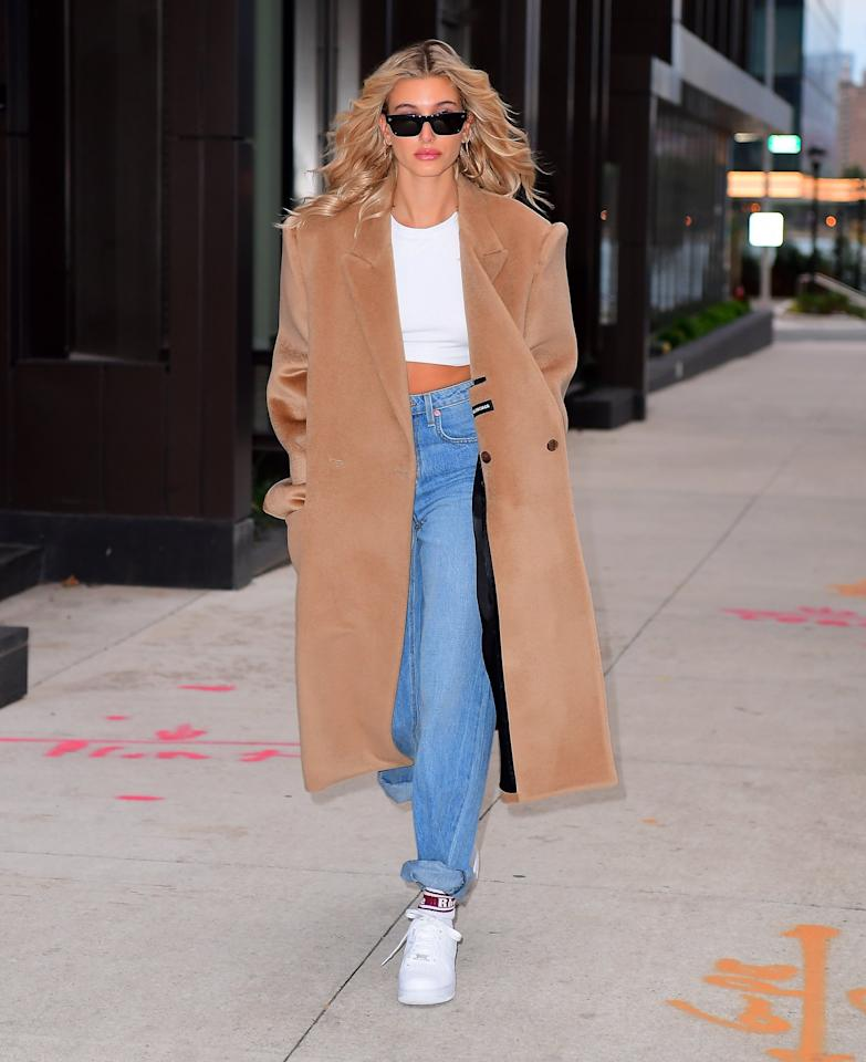 Hailey Baldwin steps out in New York City on Saturday dressed in a white crop top, denim and duster coat.