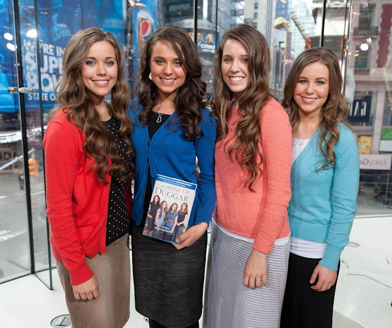 """Jessa Duggar and her sister posing for the camera with a book titled """"Growing Up Duggar."""""""