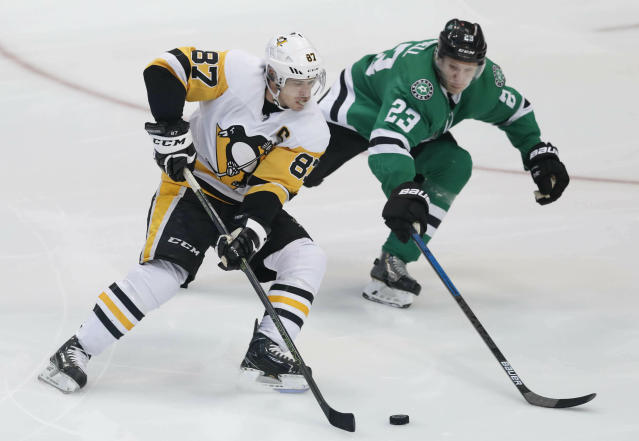 Pittsburgh Penguins center Sidney Crosby (87) and Dallas Stars defenseman Esa Lindell (23) skate for the puck during the first period of an NHL hockey game in Dallas, Saturday, March 23, 2019. (AP Photo/LM Otero)