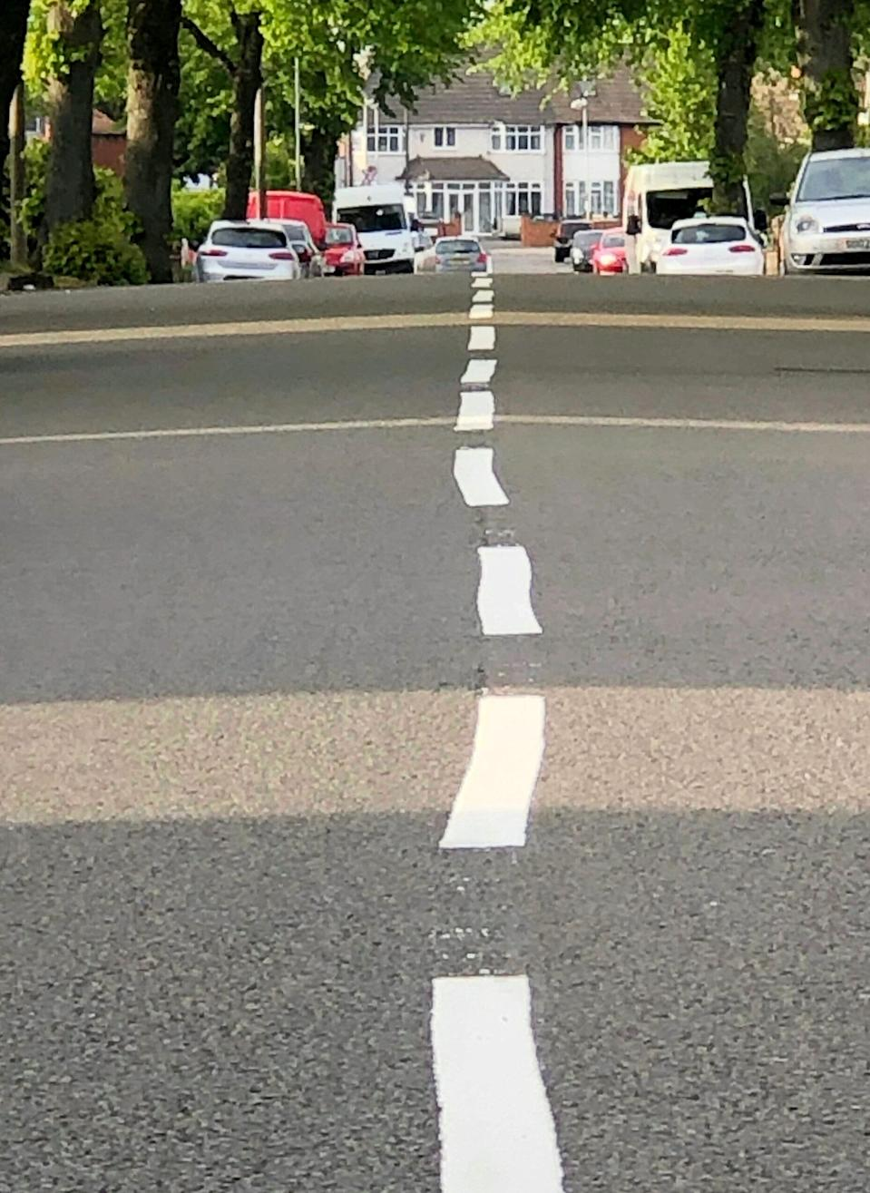 """Contractor Amey has apologised to residents after painting wonky white road markings on a city street.  See SWNS story SWMDlines.  Locals were left scratching their heads after the wobbly lines appeared in Brockhurst Road, Hodge Hill.  As well as the centre lines being out of kilter, workmen had also left paint splatters and faded lines in the road.  After visiting the street on Wednesday Councillor Majid Mahmood (Hodge Hill and Bromford) had demanded the """"shoddy"""" work be redone."""