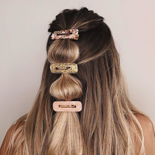 """<p>Half-up pony—but make it trendy. Use clear elastics to create a """"bubble effect"""" and then cinch each with a fun barrette.</p>"""