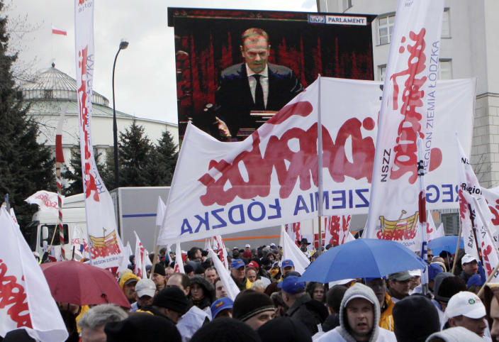 Polish workers protesting a government plan to raise retirement age to 67 turn their backs on a screen with the image of Prime Minister Donald Tusk speaking about the plan in Parliament, in Warsaw, Poland on Friday, March 30, 2012. Many blew horns to jam Tusk as he talked about the need to raise the current retirement age of 60 for women and 65 for men in order to cut thestate budget deficit. (AP Photo/Czarek Sokolowski)
