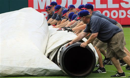The Citizens Bank Park ground crew rolls up the tarp after a brief downpour halted play during the sixth inning of a baseball game between the Philadelphia Phillies and the New York Mets, Sunday, June 23, 2013, in Philadelphia. (AP Photo/Tom Mihalek)