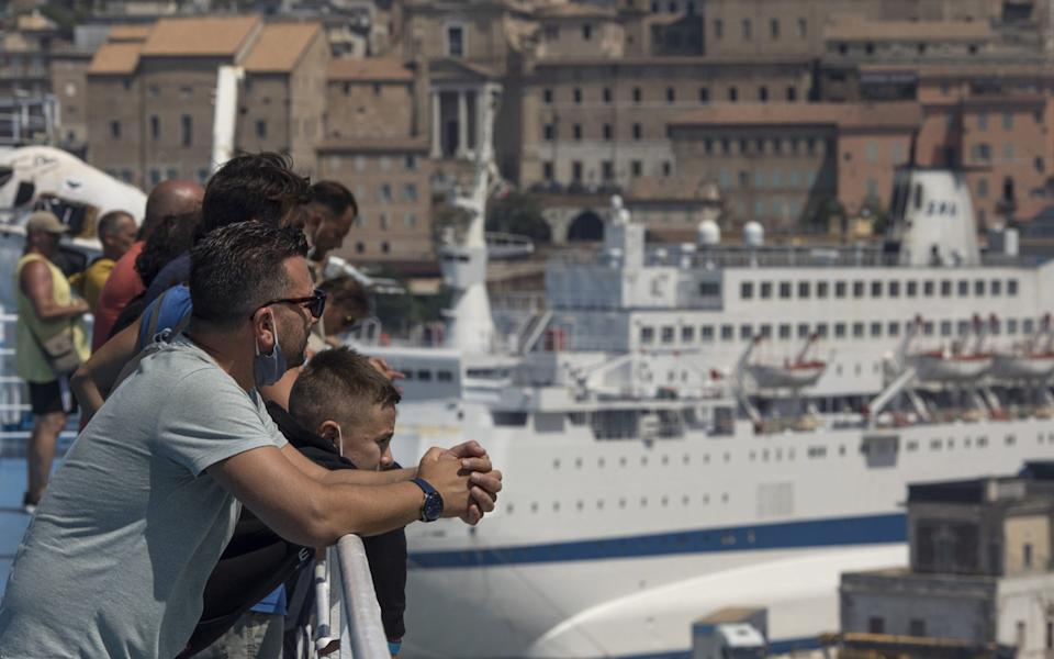 Passengers look at their arrival from the deck of a passenger ship arriving from Greece to port on August 7, 2020 in Ancona, Italy - Getty