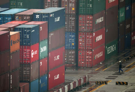 A worker walks amongst shipping containers at the port of Shanghai