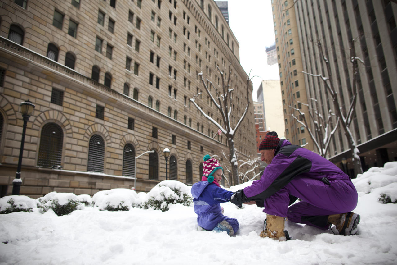 NEW YORK, NY - FEBRUARY 09: Stan Erdreich adjusts the sleeve of his daughter Marlee Bea as they play in snow in the Financial District following a major winter storm on February 9, 2013 in New York City. New York City and much of the Northeast received a foot or more of snow through Saturday morning with possible record-setting blizzard conditions expected. Heavy snow warnings are in effect from New Jersey through southern Maine. (Photo by Andrew Kelly/Getty Images)