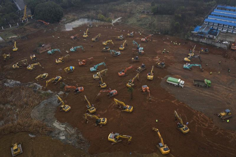 Workers driving diggers at the construction site of a hospital in Wuhan (Getty Images)