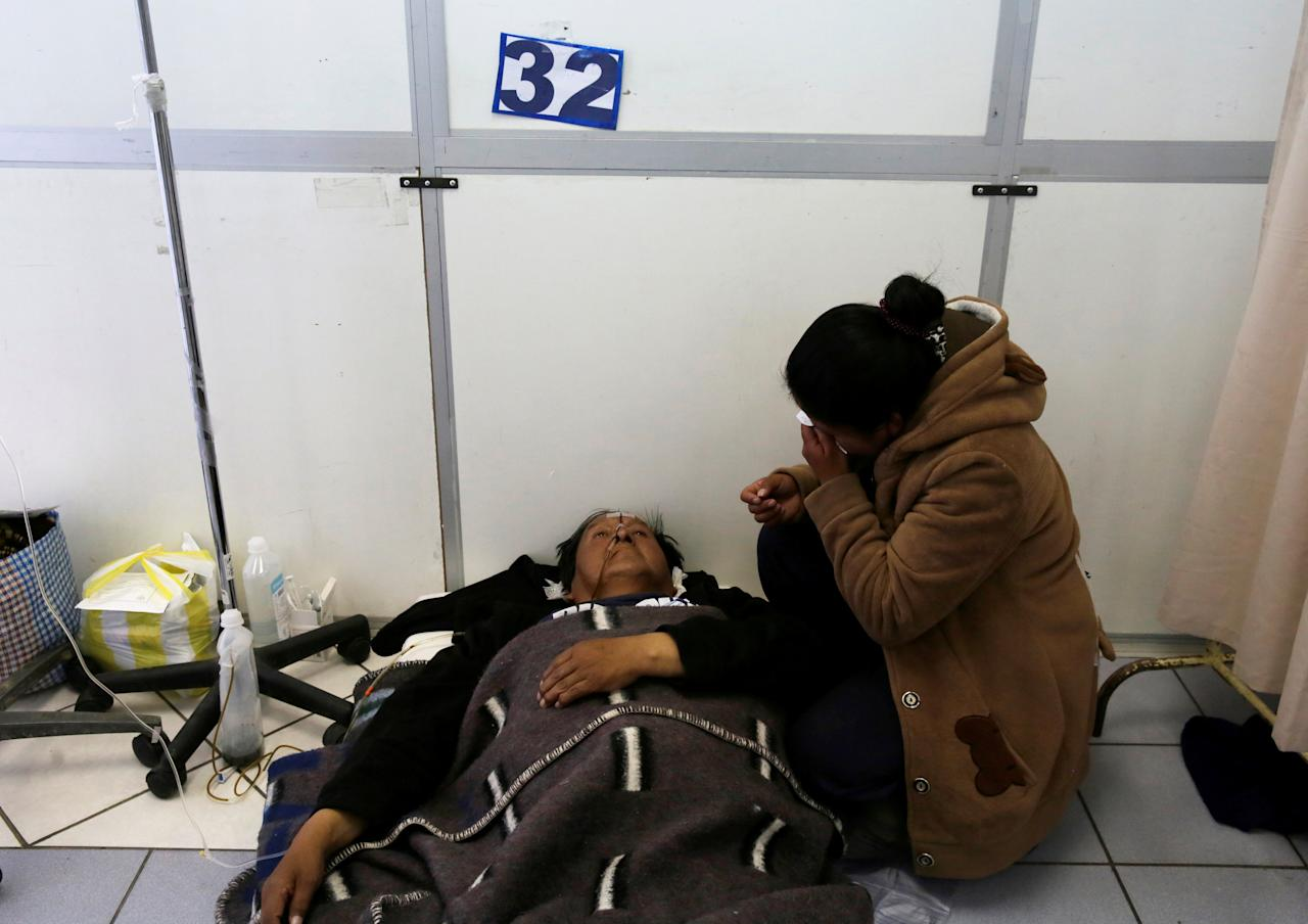 A man lies on the floor as a relative sits next to him at the emergency room of the General Hospital during a strike by healthcare employees against Bolivia's government policies for health rules, in La Paz, Bolivia, December 12, 2017.  REUTERS/David Mercado