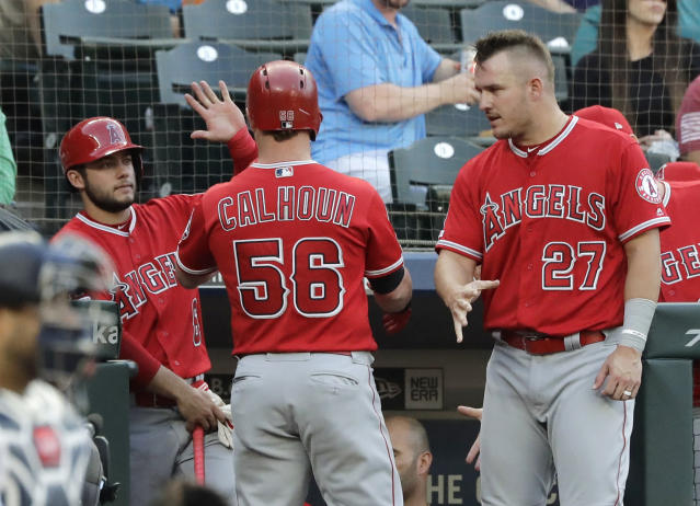 Los Angeles Angels' Kole Calhoun (56) is greeted by Mike Trout (27) after Calhoun hit a solo home run during the second inning of a baseball game against the Seattle Mariners on Thursday, May 30, 2019, in Seattle. (AP Photo/Ted S. Warren)