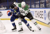 Dallas Stars left wing Jason Robertson (21) and Tampa Bay Lightning defenseman Erik Cernak (81) fight for the puck during the first period of an NHL hockey game Friday, May 7, 2021, in Tampa, Fla. (AP Photo/Jason Behnken)
