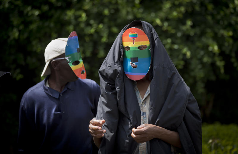 """Kenyan gays and lesbians and others supporting their cause wear masks to preserve their anonymity as they stage a rare protest, against Uganda's increasingly tough stance against homosexuality and in solidarity with their counterparts there, outside the Uganda High Commission in Nairobi, Kenya Monday, Feb. 10, 2014. Homosexuality has been criminalized in Uganda where lawmakers have recently passed a new bill, which appears to have wide support among Ugandans, that prescribes life imprisonment for """"aggravated"""" homosexual acts. (AP Photo/Ben Curtis)"""