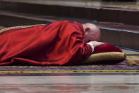 Pope Francis lies down in prayer prior to celebrating Mass for the Passion of Christ, at St. Peter's Basilica, at the Vatican, Friday, April 2, 2021. (Andreas Solaro/Pool via AP)