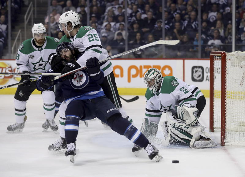 Winnipeg Jets' Mathieu Perreault (85) is wrapped up by Dallas Stars' Brett Ritchie (25) in front of goaltender Kari Lehtonen (32) during the second period of an NHL hockey game Sunday, March 18, 2018, in Winnipeg, Manitoba. (Trevor Hagan/The Canadian Press via AP)