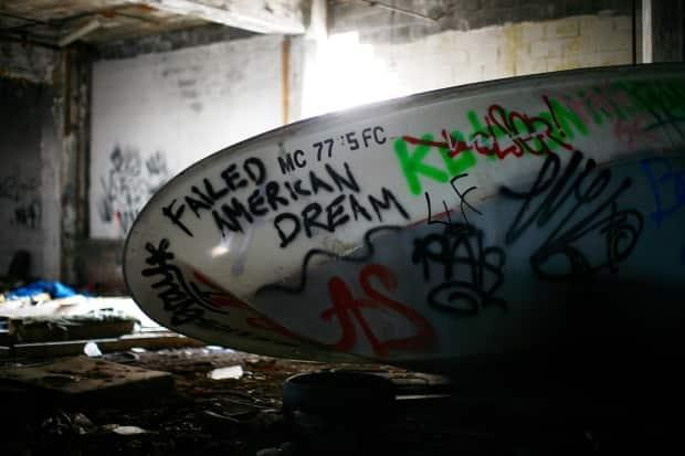 Graffiti in an abandoned Detroit factory in 2011. Governments are anxious to prevent a new round of shutdowns and layoffs like the industrial decline of the Rust Belt as business moves to places where climate rules are less onerous.  (Eric Thayer/Reuters - image credit)