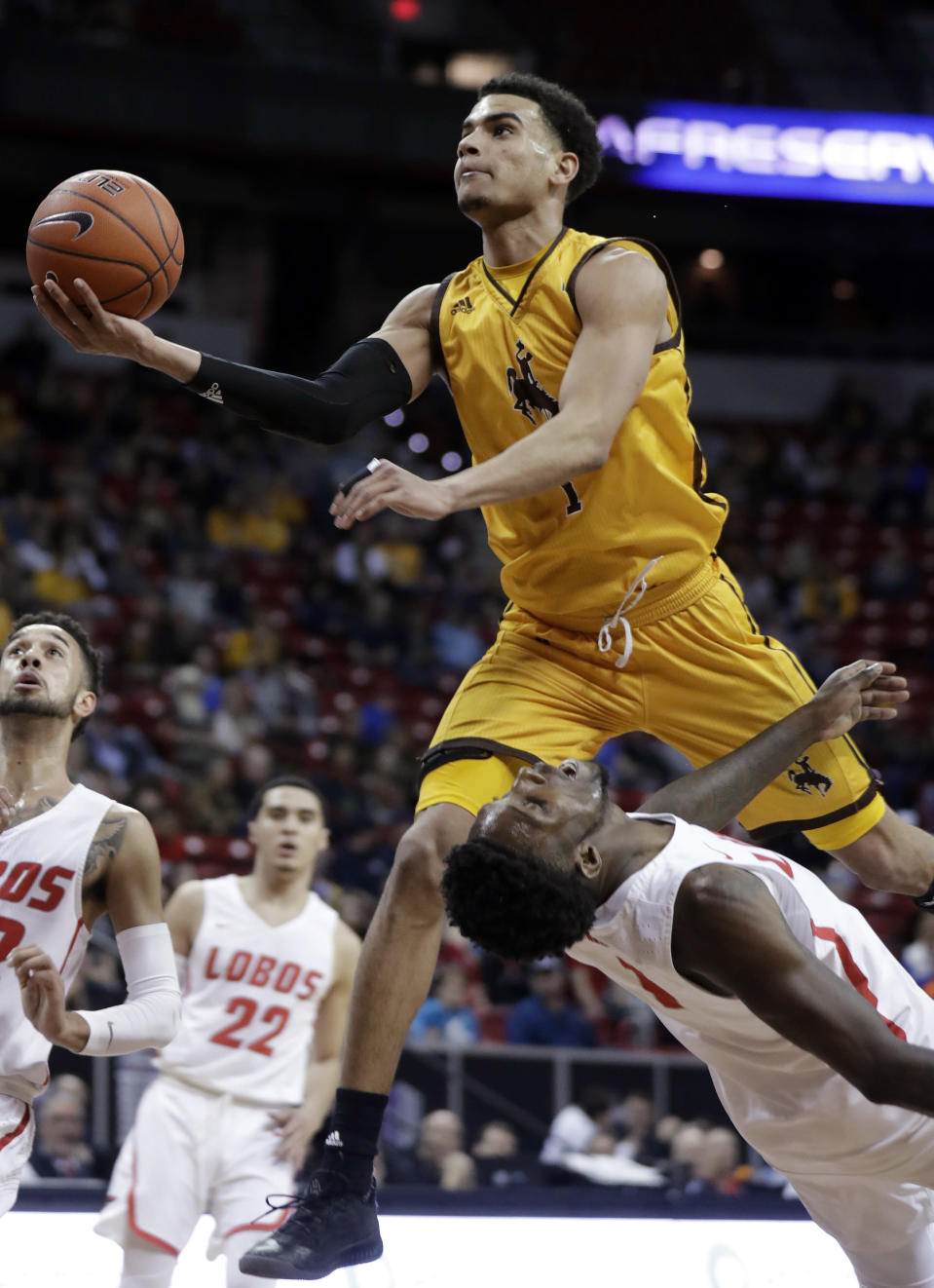 Wyoming's Justin James shoots over New Mexico's Jalen Harris during the first half of an NCAA college basketball game in the Mountain West Conference men's tournament Wednesday, March 13, 2019, in Las Vegas. (AP Photo/Isaac Brekken)