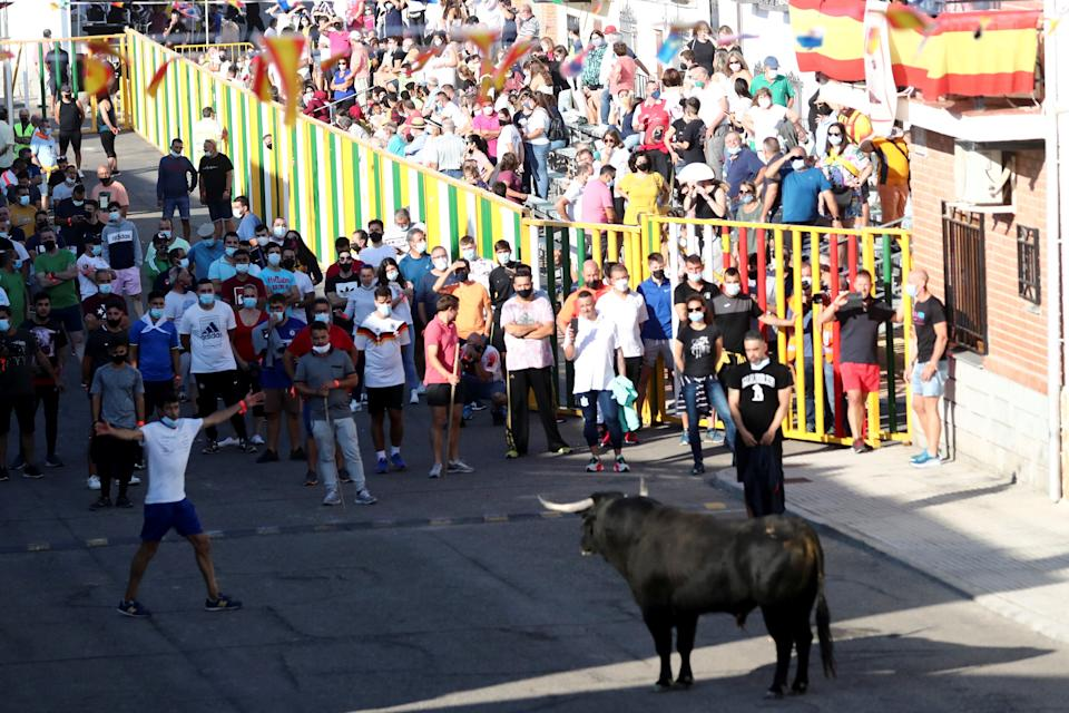 Revellers and spectators watch a steer during the first running-of-the-bull festival since the coronavirus disease (COVID-19) pandemic began in Villaseca de la Sagra, central Spain, September 5, 2021. REUTERS/Sergio Perez