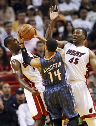 Charlotte Bobcats guard D.J. Augustin (14) goes up for a shot against Miami Heat guard Terrel Harris, left, and center Dexter Pittman (45) during the first half of an NBA basketball game, Friday, April 13, 2012, in Miami. (AP Photo/Wilfredo Lee)