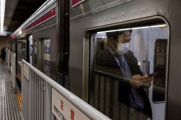 A commuter wearing a mask waits for a train to depart at Shinjuku Station in Tokyo, Monday, Jan. 27, 2020. Japan said Monday it is preparing to send chartered flights to China to evacuate Japanese citizens out of Wuhan, the epicenter of as the new coronavirus outbreak, as the death toll and the number of patients rapidly increase and transportation in and out of the city is cut off. (AP Photo/Jae C. Hong)