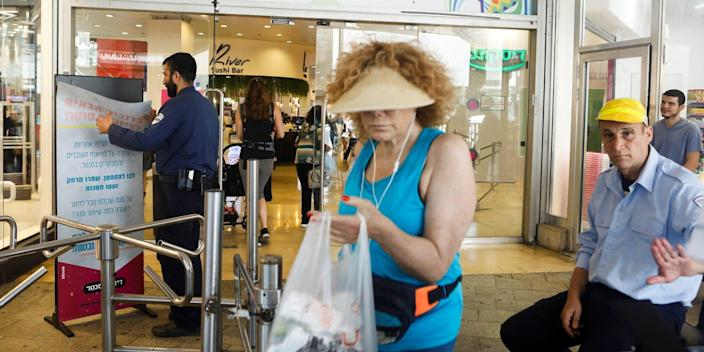 Two shoppers, maskless, use a Tel Aviv mall while a worker in the background removes a sign about COVID-19 restrictions.