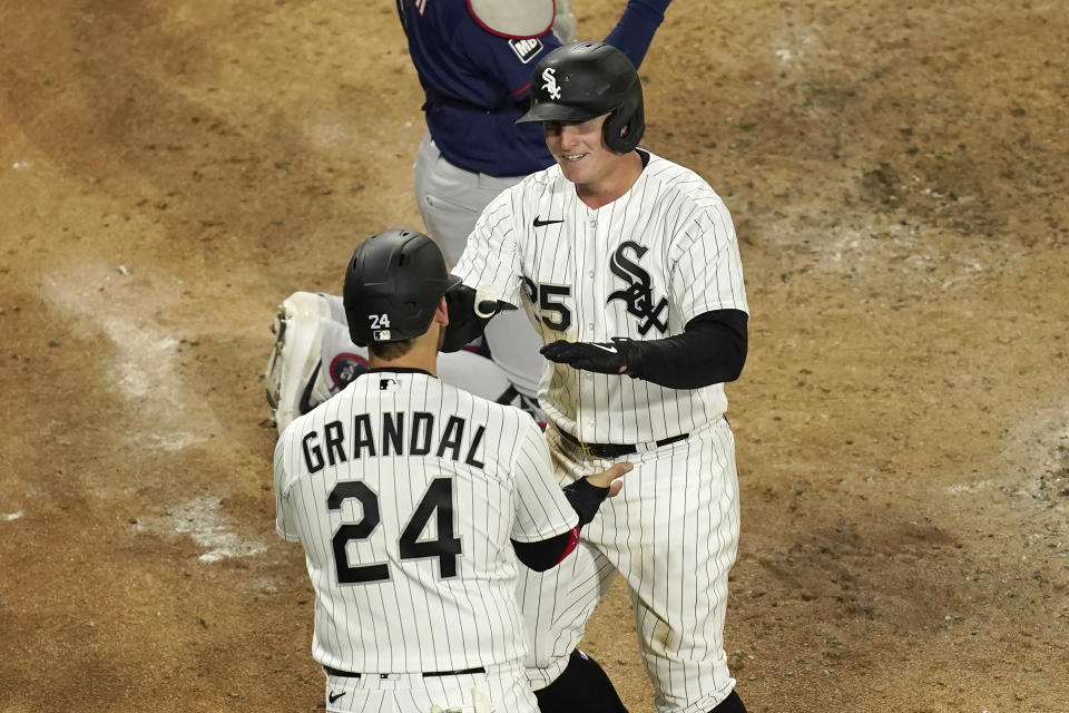 Chicago White Sox's Andrew Vaughn (25) celebrates his home run off Minnesota Twins starting pitcher J.A. Happ with Yasmani Grandal during the fourth inning of a baseball game Wednesday, May 12, 2021, in Chicago. (AP Photo/Charles Rex Arbogast)