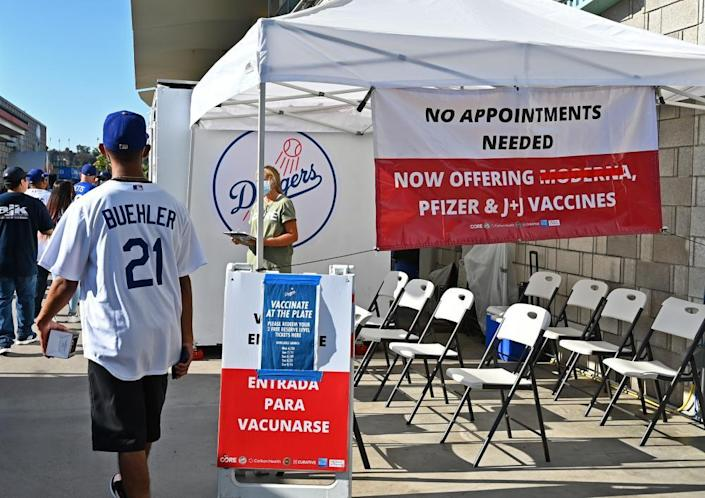 A man in a Los Angeles Dodgers hat and jersey walks past a tent with signs offering free game tickets for each vaccine taken before a game.