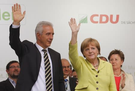 German Chancellor Merkel and Saxony State Premier Tillich, who runs as candidate for the Christian Democratic Union (CDU) in the upcoming Saxony state election, wave to supporters at an election campaign in Dresden
