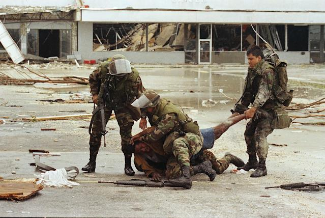 <p>Members of the Florida National Guard subdue a man outside the Cutler Ridge shoe store after the guard found the store wide open. The unidentified man, carrying a firearm, was wrestled to the ground after guard members though he was looting the store. There was no evidence he was looting. (AP Photo/Lynne Sladky) </p>