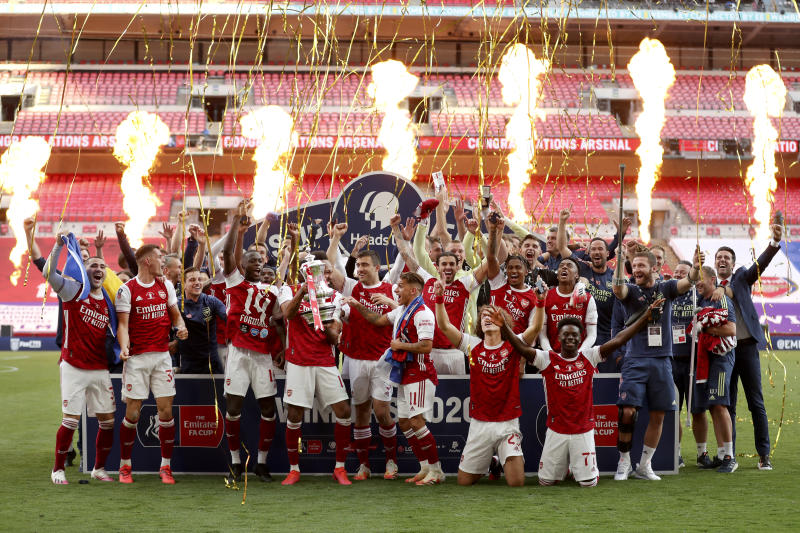 Pyrotechnics go off as Arsenal's players celebrate with the trophy after the FA Cup final soccer match between Arsenal and Chelsea at Wembley stadium in London, England, Saturday, Aug.1, 2020. (Catherine Ivill/Pool via AP)