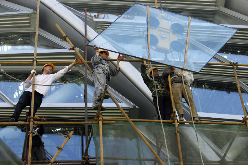 Workers guide a glass panel as it is positioned at the construction site of a modern commercial building in Beijing, China, Wednesday, May 30, 2012. China is rolling out a mini-stimulus to fight its economic slump but is moving cautiously after its massive response to the 2008 global crisis left a painful hangover of inflation and debt. (AP Photo/Ng Han Guan)