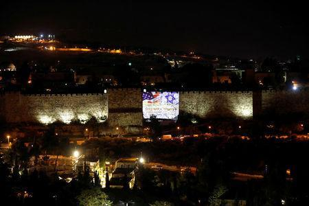 An Israeli national flag and an American one are projected on a part of the walls surrounding Jerusalem's Old City December 6, 2017. REUTERS/Ronen Zvulun