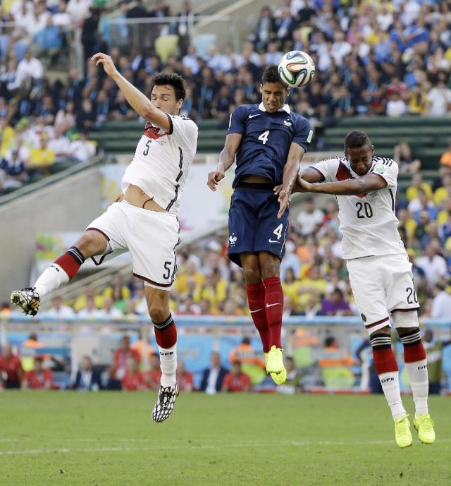 France's Raphael Varane heads the ball between Germany's Mats Hummels and Jerome Boateng (20) during the World Cup quarterfinal soccer match at the Maracana Stadium in Rio de Janeiro, Brazil, Friday, July 4, 2014. (AP Photo/Kirsty Wigglesworth)