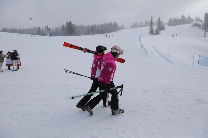 Skiers hold skis as they enjoy first day after loosening coronavirus disease (COVID-19) restrictions at ski slope in Jurgow