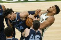 Milwaukee Bucks' Giannis Antetokounmpo and Memphis Grizzlies' Dillon Brooks battle for a loose ball during the first half of an NBA basketball game Saturday, April 17, 2021, in Milwaukee. (AP Photo/Morry Gash)