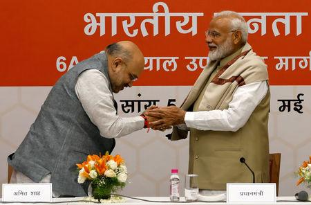 India's Prime Minister Narendra Modi shakes hands with the Bharatiya Janata Party (BJP) President Amit Shah during a thanksgiving ceremony by BJP leaders to its allies at the party headquarters in New Delhi, May 21, 2019. REUTERS/Anushree Fadnavis/Files