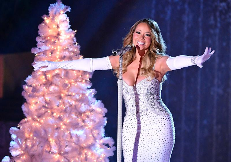 mariah carey wearing a white sequined dress and white gloves, singing into a microphone in front of a white christmas tree