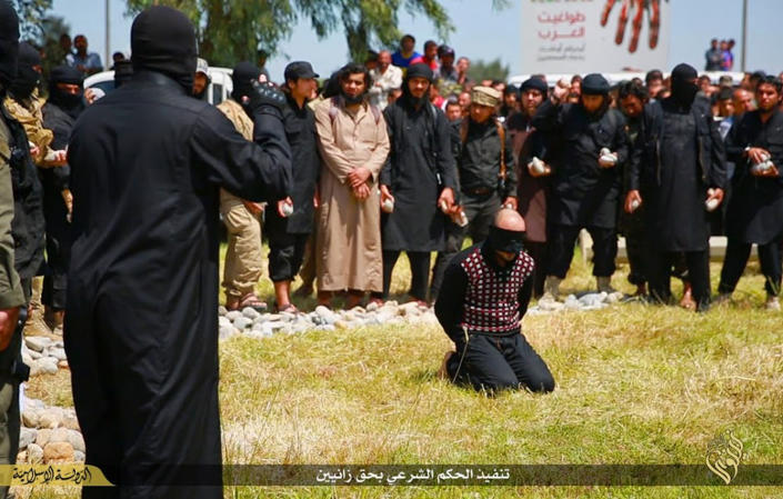 In this photo released on April 27, 2015, by a militant website, which has been verified and is consistent with other AP reporting, Islamic State militants gather around a man, center, knees on the ground, as they prepare to execute him, in Mosul city, north Iraq. A US-based Syrian rights group is compiling evidence against Islamic State militants who were part of one of the extremist group's most powerful bodies of governance used to regulate daily life and impose and execute penalties. (Militant website via AP)