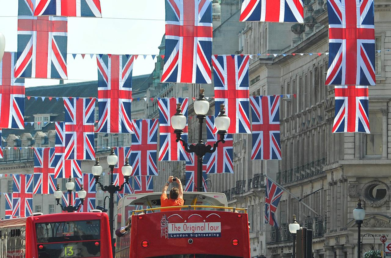 A tourist photographs Union flags hung along Regent Street in celebration of the forthcoming royal wedding between Prince William and Kate Middleton in London, Britain April 19, 2011. REUTERS/Toby Melville/File Photo