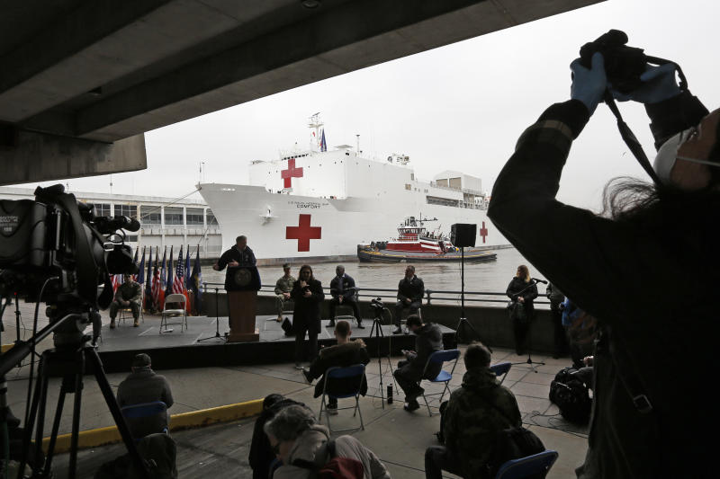 A journalist records speakers at a press briefing following the arrival of the USNS Comfort, a naval hospital ship with a 1,000 bed-capacity, March 30, 2020, at Pier 90 in New York. The ship will be used to treat patients who do not have the new coronavirus as land-based hospitals fill up to capacity with those that do. (AP Photo/Kathy Willens)