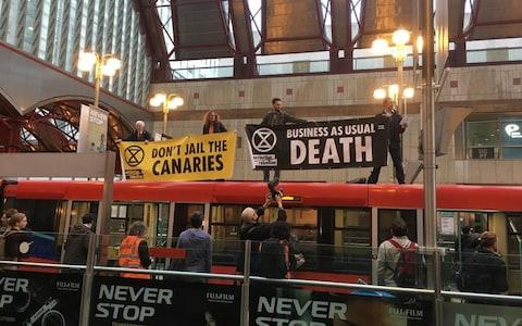 Activists climbed on top of a train at Canary Wharf station - Credit: Jack Hardy
