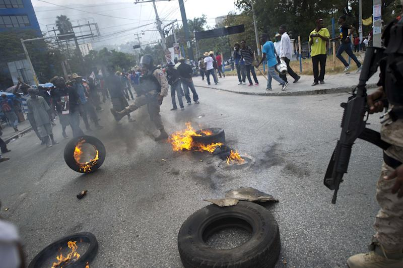 Haitian police remove a barricade of burning tires placed by anti-government protesters during a march against the government of Haitian President Michel Martelly in Port-au-Prince on January 10, 2015 (AFP Photo/Hector Retamal)