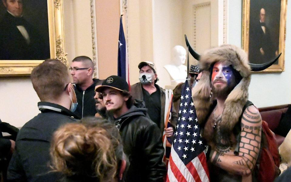 Jake Angeli (R) is seen inside the US Capitol building during the pro-Trump riots - Mike Theiler /Reuters
